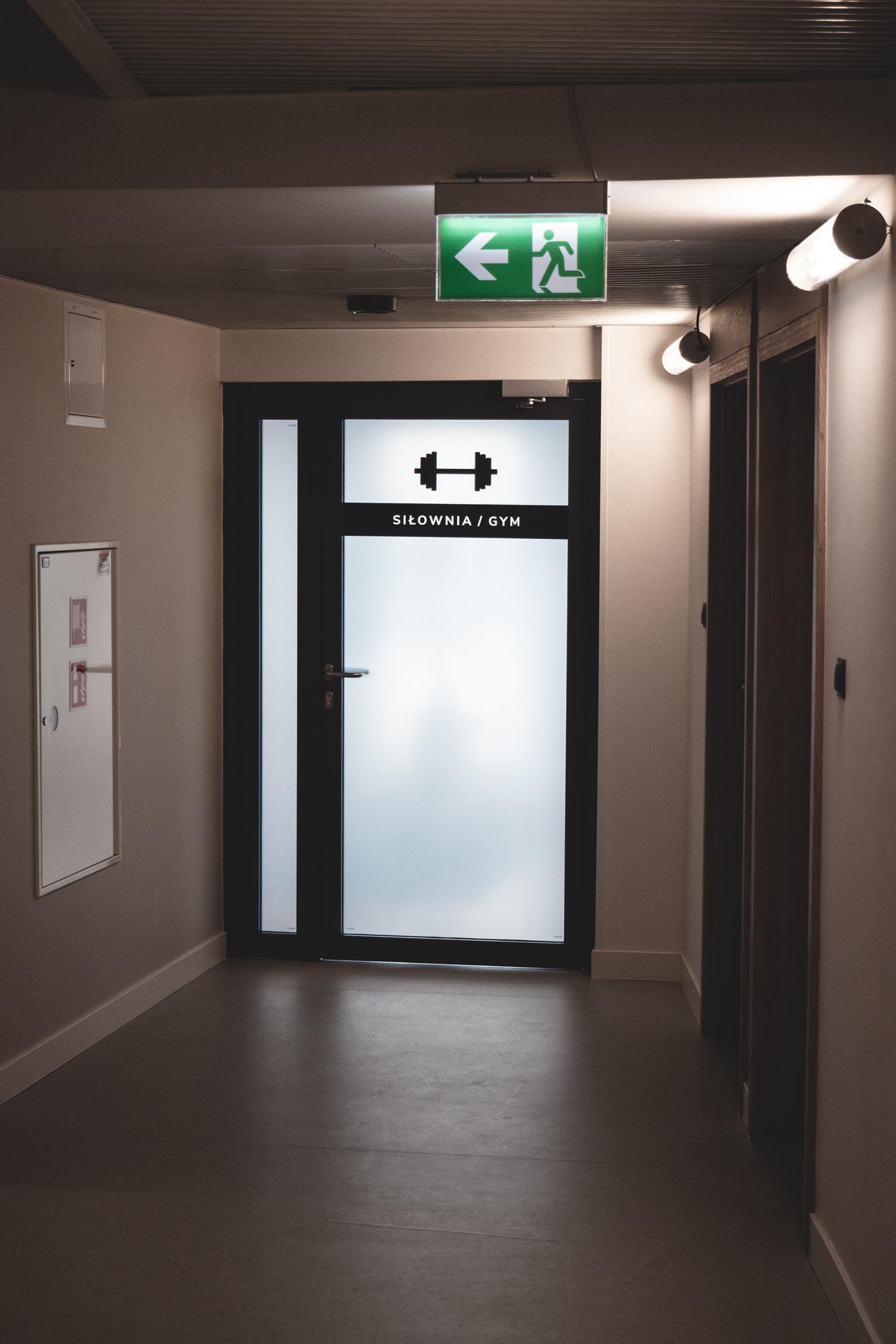 Drzwi do pomieszcvzenia siłowni oklejone folią szronoiną z grafiką z czarnej foli